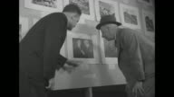 'Press Pix Prizes Given for Best News Photos' / in gallery in Empire State Building two women and man look at photographs on wall / Al Smith former...