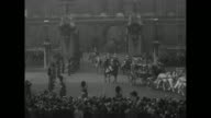 'Queen Opens Parliament' superimposed over royal coach rolling past crowd / Irish State coach carrying Queen Elizabeth and Prince Philip rolls...