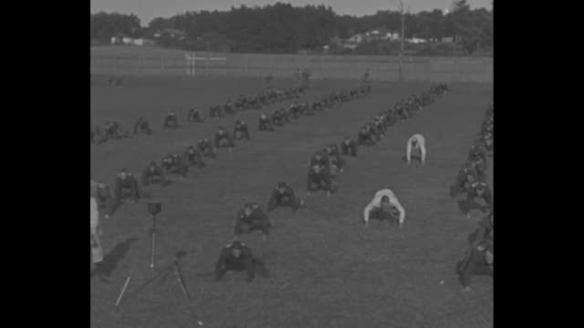 'Rockne's Irish Don Grid Togs South Bend Ind Coach Rockne starts Fall training at Notre Dame' / two shots of players in lines on field doing...