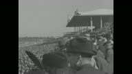 'Rosemont Wins Richest Race by a Whisker' / title 'Arcadia Calif' superimposed over paddock with horses and crowds at Santa Anita Park before running...