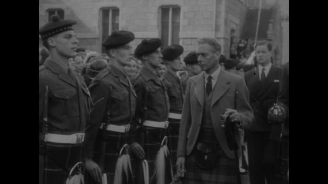 'Royal Family on Vacation in Scotland' superimposed on marching men in kilts / George VI in kilt / rows of Scottish military men / George reviewing...