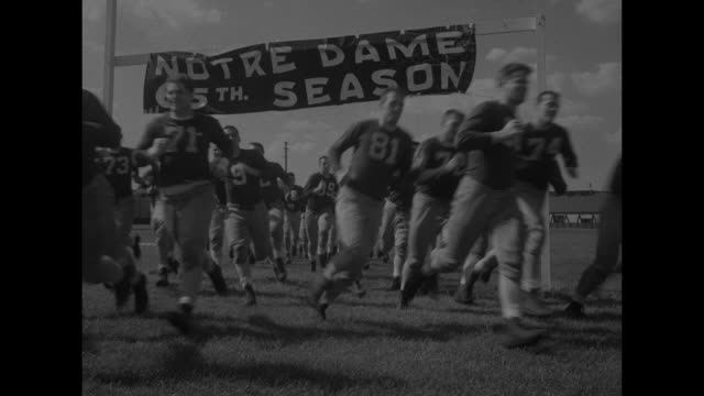 'Sports Fighting Irish Limber Up For Busy Fall' superimposed for Notre Dame football team running onto field / team workout / tackle practice with a...