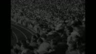 'SPORTS' / title card 'European Games BANNISTER RED ATHLETES STAR' superimposed over start of 1500meter race / crowd looks on / racers move away as...