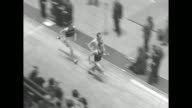 'Sports' / Title card 'K of C Track Meet' superimposed over high shot racing track at Madison Square Garden spectators in foreground stand as racers...