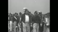 'The Babe Goes Country Club' / various shots of Babe Ruth and baseball players parading on field in Napoleonic era Navy costumes accompanied by drum...