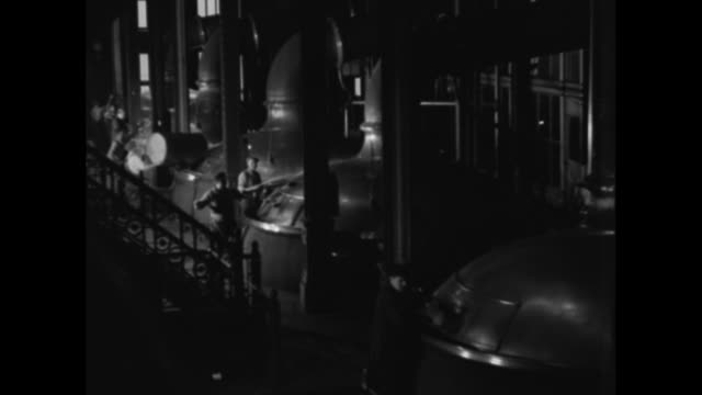 'The beer that made Milwaukee famous flows freely again' / Joseph Schlitz Brewing Company workers clean the outside of huge metal brewing vats and...