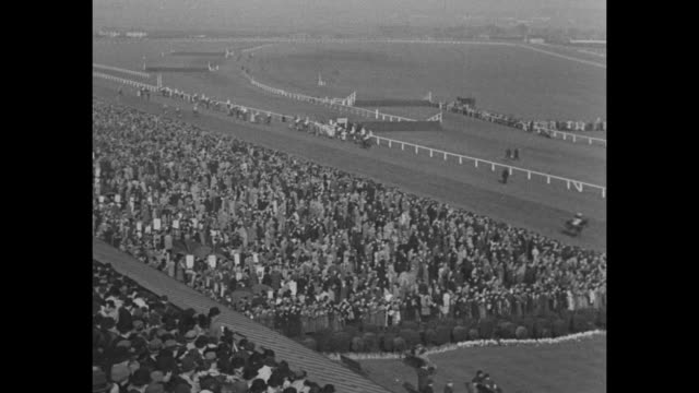'The Grand National' superimposed over horses steeplechase racing at the Aintree Racecourse / crowds watch the race / King George VI and wife Queen...