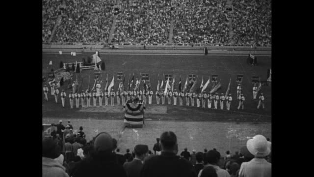 'The Greatest Olympic Games in history end the torch goes out to burn again in Berlin in 1936' / color guard present country flags behind podium on...