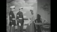 'Toys for Tots Marines open Yule Drive' superimposed over two Marines in dress uniform walking on studio lot / MS two US Marines and actress Natalie...