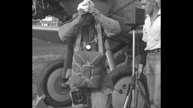 'What To Wear Parachuting Washington Scott Navy star dons garb to be worn in 30000 foot leap' / close view of man standing next to airplane with...