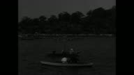 'Yale Oarsmen Beat Harvard' / aerial view of boats in Thames River / moving shot of boats in river from observation train / Harvard junior varsity...