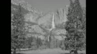 'Yosemite' superimposed over beauty shot Yosemite Falls with trees in foreground / tiltup shot wooden cross with sun peering over mountain in...