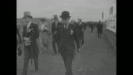 'First Pictures MidDay Sun Wins Derby' / race is nicknamed the 'Coronation Derby' / people arriving / men in formal attire morning coats and top hats...
