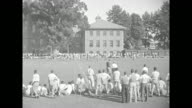 'Trojans Train on Gridiron' / various shots of USC Trojans players playing a scrimmage on practice field at university campus with crowd watching...