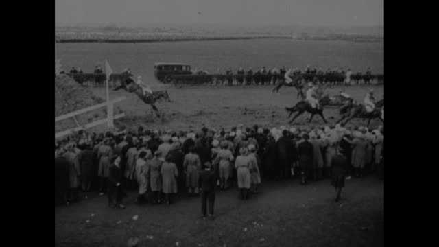 Title 'Grand National 36 Horses 34 Spills' superimposed over horses on track at Grand National at Aintree Racecourse / VS people placing bets / VS...