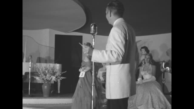 'Miss Canada of 1952' superimposed over woman in crown and two others / Marilyn Reddick crosses stage in evening gown and walks behind emcee / row of...