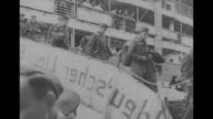 'More Prisoners Repatriated Through Spain' / shot of Casablanca harbor / shot from below of freed prisoners on ship with swastika on its side / three...