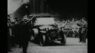 'Roses of France' / US Gen John J Pershing seated in rear seat of open car is handed bouquet of roses by small girl / automobiles belching exhaust...