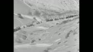 'Ski Jumping ' superimposed over WS people walking along trail between snow covered slopes / two closer views of people walking along trail / skier...