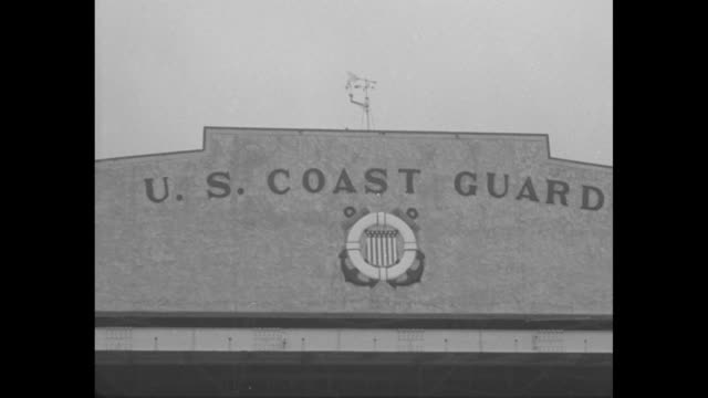Title 'Spring Storm Warning' superimposed over stormy ocean seen through trees / top of Coast Guard hangar with emblem below words reading 'U S Coast...