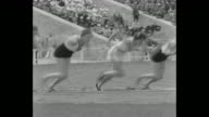 Title superimposed on women at racing starting block '100 Meter ' / race begins / high angle view of racers far below and packed grandstands / US's...