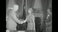 Title superimposed over Dace Epermanis '150000th DP is Welcomed by Truman' / Dace walks up shakes Pres Harry Truman's hand in the oval office and...