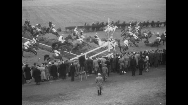 'The Grand National' superimposed over crowds and grandstand at Aintree Racecourse with fog in background / horses begin steeplechase race as starter...