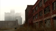 ZO to ANGLED WS Abandoned dilapidated warehouse w/ broken windows amp some graffiti weeds amp grass FG FOGGY cityscape BG MI NOT Dry Dock recession...