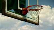 PAN to ANGLED MS Rim w/ net of basketball hoop glass backboard slightly dilapidated green basketball stand beam BG cloudy sky BG Sports outdoor court
