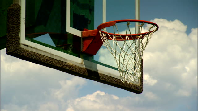 PAN to ANGLED MS Rim w/ net of basketball hoop glass backboard slightly dilapidated green basketball stand beam BG cloudy sky BG Sports outdoor court
