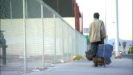 PAN to WS BACK of unidentifiable African American homeless man walking away from frame down street pulling luggage cart w/ large blue sack bag Poor...