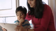 PAN to boy, 3-5 years old, sitting with his Mum watching video on digital tablet