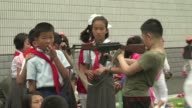 To celebrate North Korean Children's Union Day the pupils of Pyongyang Number Four Primary School throw mock grenades at targets crawl under a frame...