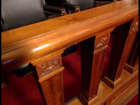 TU to empty jury box seats behind wooden barrier Jury duty verdict trial law judicial guilty not guilty innocent deliberation