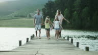 WS to MS of family walking along jetty by lake