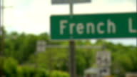 PAN to IN FOCUS MS French Lick green sign partial rural town trees BG including sign for Indiana 56 IN