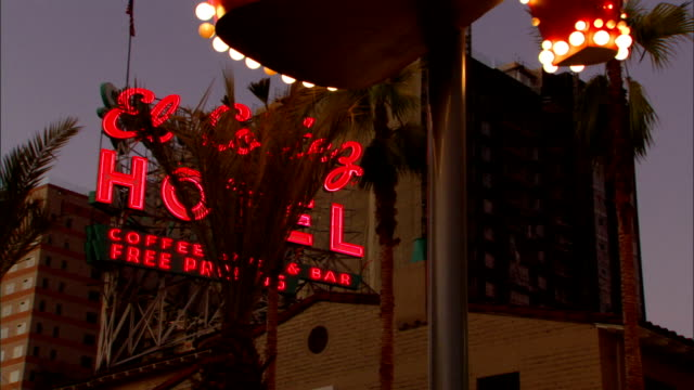 To lit neon sign statue of showgirl lights flashing partial El Cortez hotel casino building BG on Fremont Street NV downtown