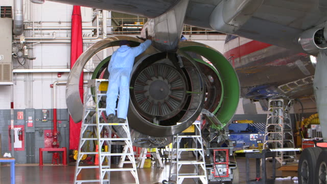 ZI to mechanic working on jet engine on plane in hanger/DFW International Airport, Dallas-Fort Worth, Texas, USA