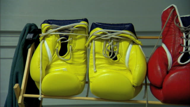 PAN to MS Pair of yellow red boxing gloves on rack in unidentifiable area Sports equipment no brands