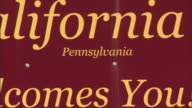 SIGN HD TU to WS Sign along highway w/ various advertisement signs around Working Together as One the community of California Pennsylvania Welcomes...