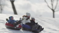 Tobogganing on a hill with friends