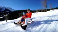 tobogganing on sunny winter day
