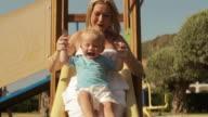 Toddler and his mother on slide/Benhavis, Marbella region, Spain