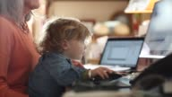 Toddler boy grandson being taught how to use a computer by his senior grandmother