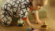 Toddler boy playing with toys on a seating bench in living room