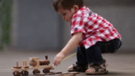 Toddler boy playing with wooden train toy on terrace