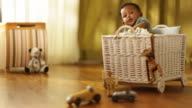 Toddler boy sitting in rattan basket in kids room