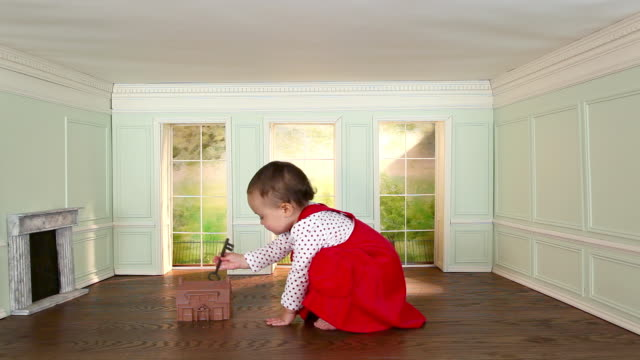 Toddler girl in small room with model house and key