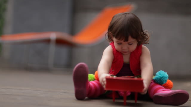 Toddler girl playing mini piano on terrace