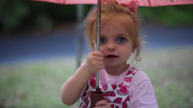A toddler girl walks around outdoors under a pink umbrella.
